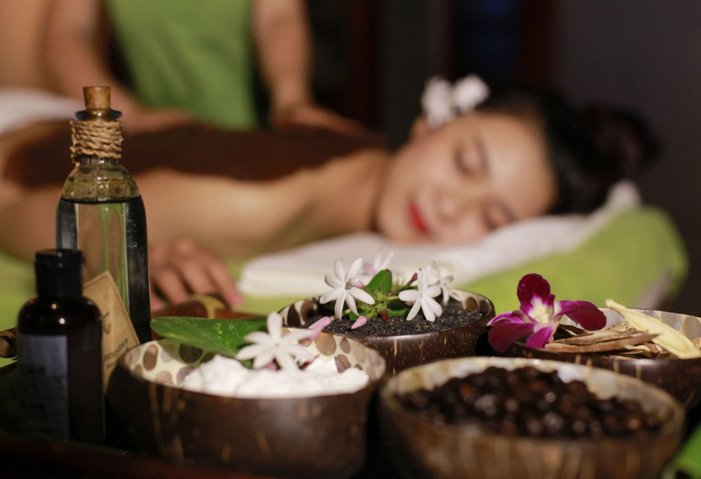 Woman receiving massage in background while essential oils and aromatics are shown in foreground.